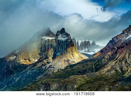 Travel in Chile. National Park Torres del Paine. Black cliffs of Los Kuernos. Hurricane wind blows cold clouds. The concept of active and adventure tourism