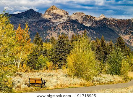 Bench by a path with view of the Grand Tetons mountains