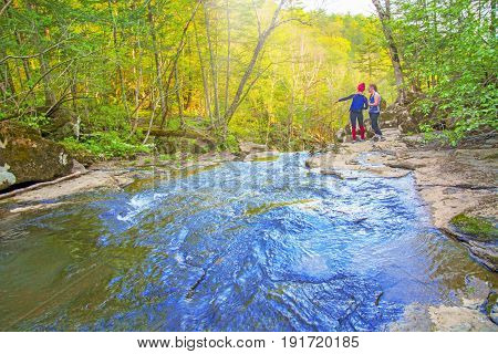 two girls stand on the waterfall, view from the top of the waterfall falling down, tourists with forest waterfall