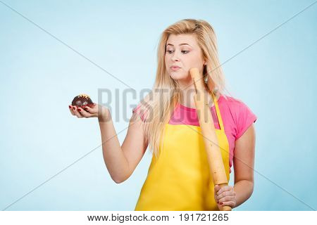 Woman Holding Cupcake And Rolling Pin Wearing Apron