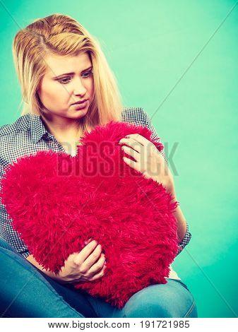 Break up divorce bad relationship concept. Sad depressed woman holding big red fluffy pillow in heart shape she needs love.