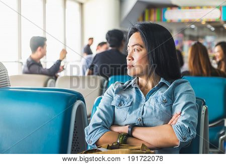 asian Woman waiting for flight at airport terminal for departure Abroadtravel concept.