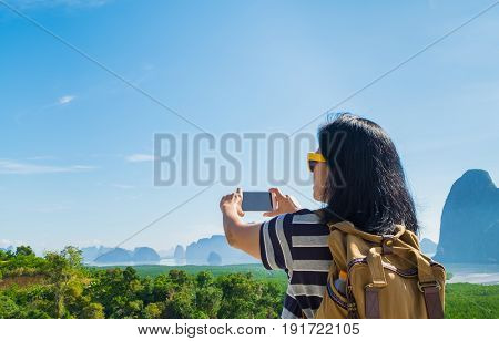Young traveler woman backpacker use mobile phone take a photo of beautiful of nature at top of mountain and sea viewFreedom wanderlust conceptKhao Samed Nang CheePhang NgaThailand