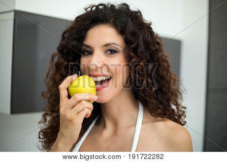 Beautiful woman eating a green apple