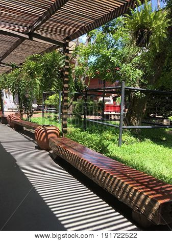 Summer garden decoration light and shadow of wooden slat shelter on log long benches.