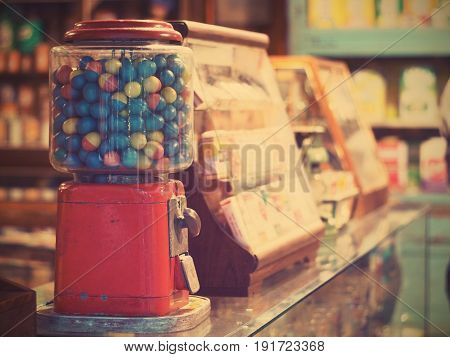 gamble eggs in vintage gumball machine on glass counter at grocery store vintage filter effect