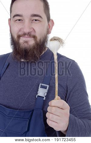 Portrait of a young bearded farmer with garlic in his hands