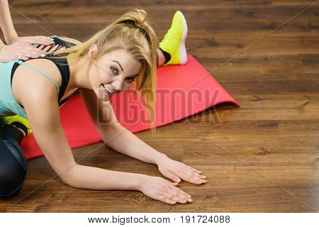 Young blonde woman in sportswear stretching body working out with her trainer. Training at home being fit and healthy.