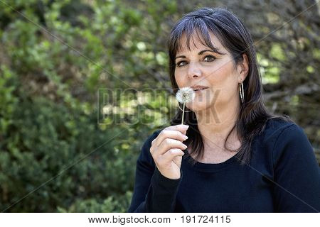 Middle Aged Woman Blowing On A Dandelion Pod