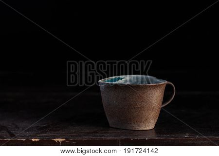 Old ceramic cups and dusty on a wooden table.