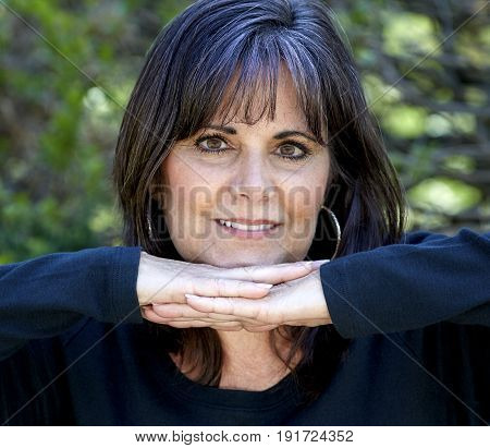 Middle Aged Woman Smiling With Hands Under Chin