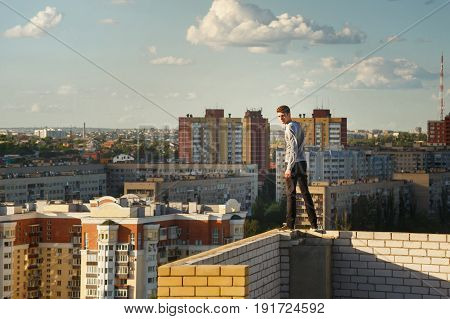A lone roofer walks along the edge of the roof fence on a high-rise building. Courage and adrenaline. Against the backdrop of the cityscape.