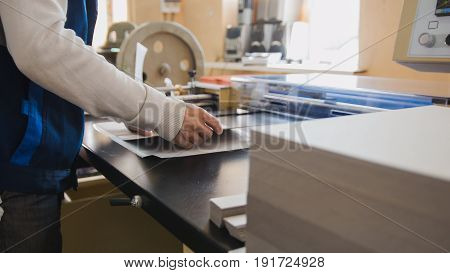 Print operator pulls printed sheet of paper, polygraphic process