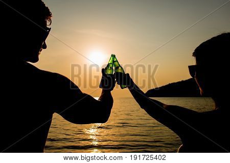 Couple clanging bottles of beers celebrating on holiday at the beach in summer sunset
