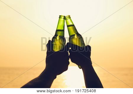 Couple Hands Holding Beer Bottles, Clanging At The Beach In Summer Sunset