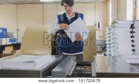 Man worker near printing machine, polygraph industry, close up