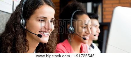 Group of multiethnic smiling call center team - panoramic web banner