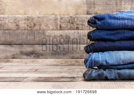 Stack of folded blue jeans on old wood background with copy space