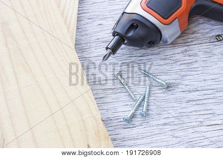 Carpentry Tools a cordless electric screwdriver and screws