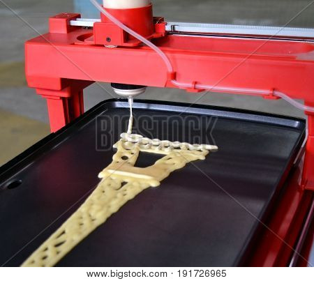 3d printer that printing a liquid dough. 3D printer printing pancakes with liquid dough different shapes close-up. Modern additive technologies 4.0 industrial revolution