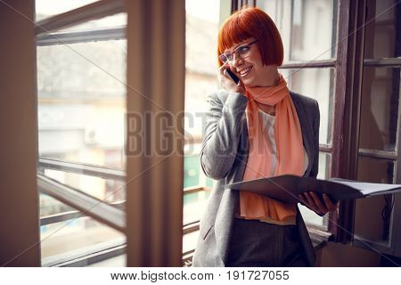 Young woman by window in office arranging meetings with cell phone
