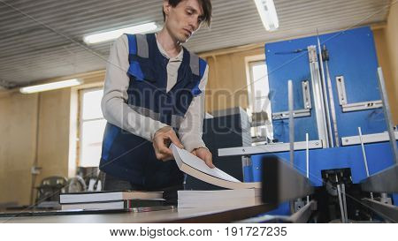 Worker inserts sheets of paper to printing machine, polygraph industry, close up