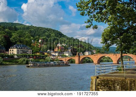 Heidelberg, Germany - June 4, 2017: River Nickar Embankment, Touristic Boat, Old Bridge And A Hill A