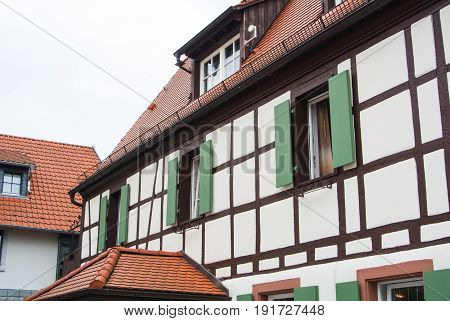 Traditional German Village Half-timbered House With Wooden Decoration And Green Shutters Of The Vind