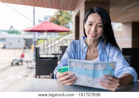Woman use of city map and cellphone in Hong Kong
