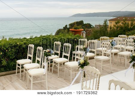 Little Bouquets Beautified With Blue And White Flowers Put On The Chairs' Backs