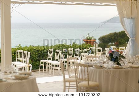 Wedding By The Sea. White Chairs Stand On The Porch With Greenery