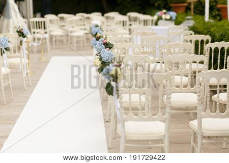 White Chairs Decorated With Blue Hydrangeas Stand By The Path To Wedding Altar