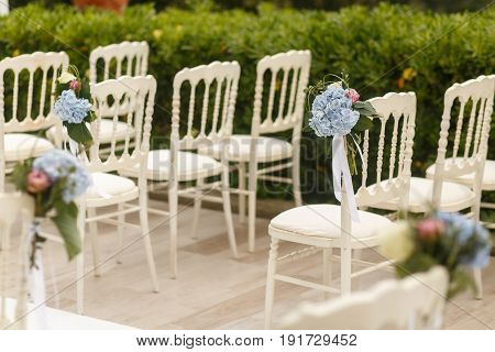 Blurred Picture Of Blue Hydrangeas Put On White Chairs