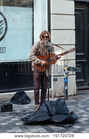 Copenhagen Denmark - August 11 2016. Busker playing guitar and singing in pedestrian street in Copenhagen