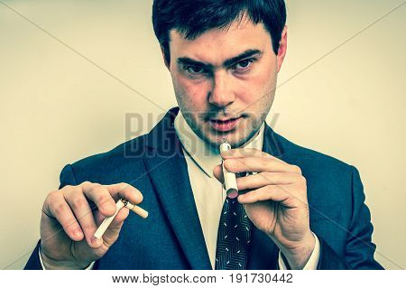 Businessman in suit is comparing electronic cigarette and tobacco cigarette - retro style