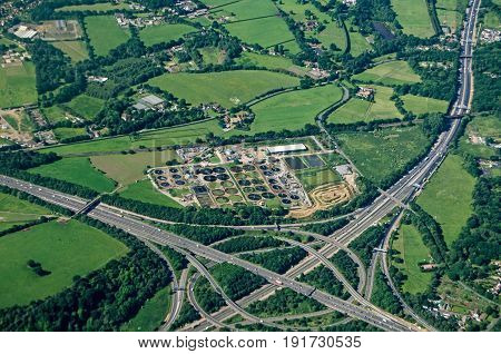 View from a plane of the Thorpe Interchange junction between the M25 and M3 motorways in South West London. A Thames Water sewage treatment plant is right next to the busy roads in Virginia Water Surrey.
