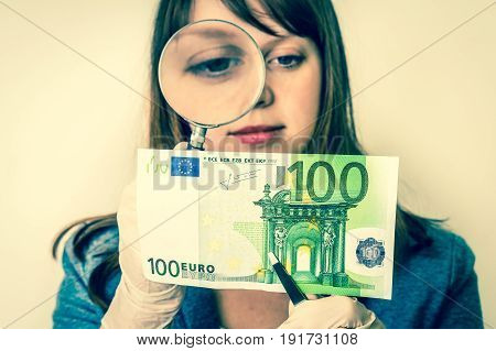 Woman Viewing Counterfeit Banknote With Magnifying Glass