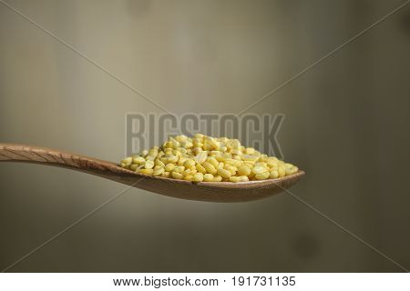 Close up mung bean is peel off on wooden spoon with wooden background.