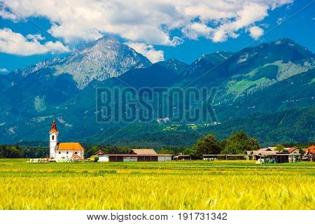 Beautiful summer landscape of a small village with an old chapel in Slovenia. Picturesque mountain range with green hills and forest. Wide angle panorama mountains against the blue sky with clouds.