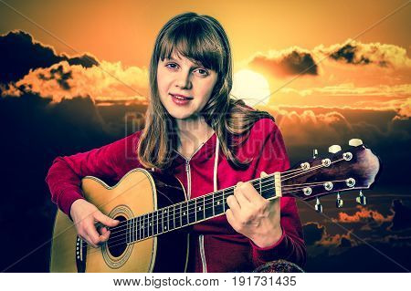 Young girl playing acoustic guitar at the sunset - retro style