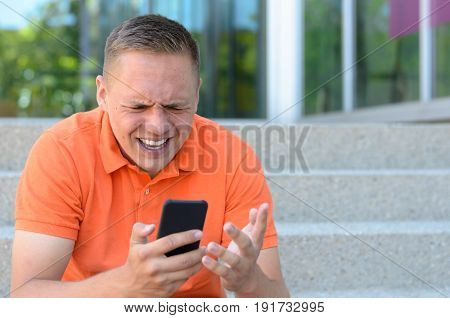 Frustrated Young Man Gesturing At His Mobile Phone