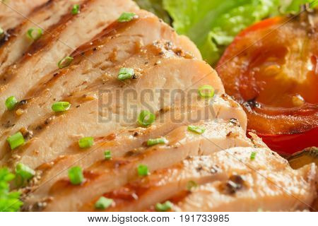 Sliced chicken breast barbecue on white plate served with grilled vegetable. Delicious chicken breast steak and salad for dinner. Homemade chicken breast barbecue on wood table for background. Chicken barbecue or pork steak close up view.
