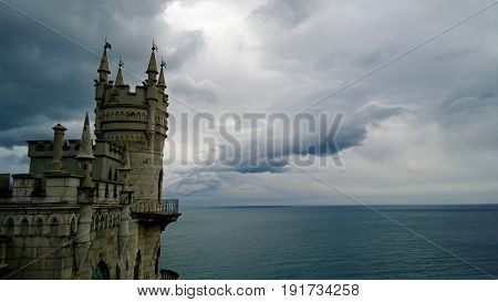 Famous landmark South of the Crimea - the Swallow's nest castle in cloudy weather. Calm Black sea and the beautiful clouds