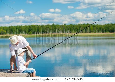 The father teaches his son to fish on the river from the pier