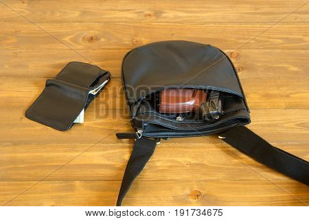 Bag with a gun and purse with money lies on a dark table