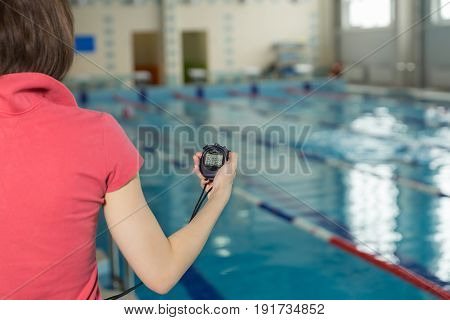 Swimming Coach Holding Stopwatch Poolside At The Leisure Center.