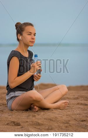 Fitness runner woman drinking water or energy drink of a sport bottle. Athlete girl taking a break during run to hydrate during hot summer exercise on beach. Healthy active lifestyle.