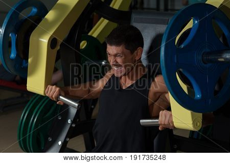 Tanned muscular man doing strength training on exercise machine in sport gym. Active lifestyle fitness club. Fit strong athlete workout with weight
