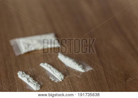Lines And Plastic Packet Of Cocaine On Wooden Table