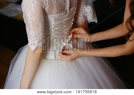 Bridesmaid is helping the bride to dress. Closeup photo of beautiful bride tying up her wedding dress.
